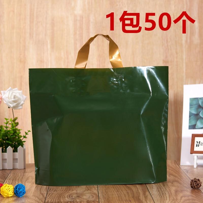 新しいショッピングバッグに厚いプレゼント袋を入れて、男性の女装子供服の服屋さんの手で袋を持って、濃い緑のビニール袋を卸売りします。