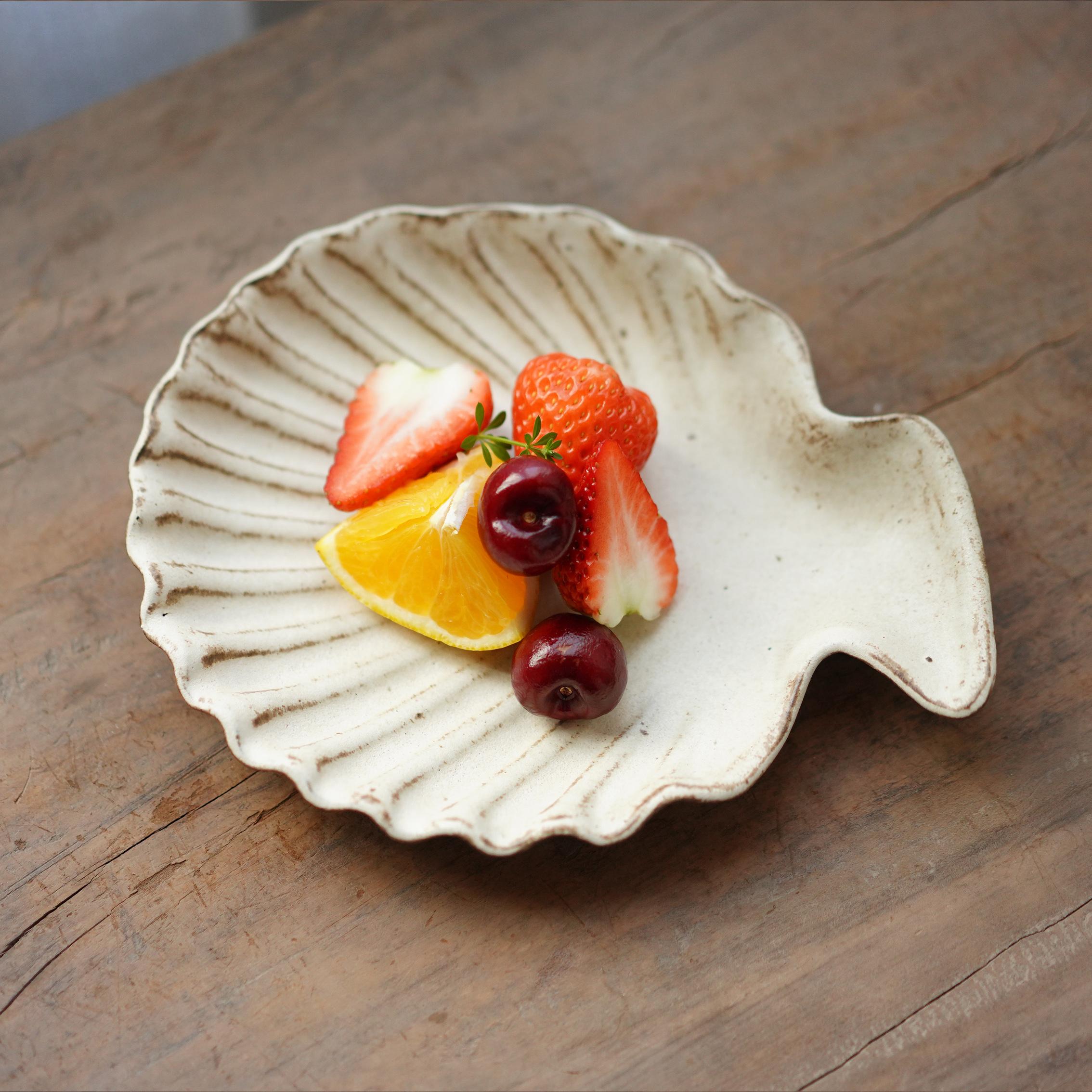 粗雑な陶の自由な造型の貝殻の皿の陶磁器の食器