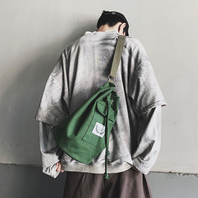 帆布斜挎包男士学生韩版ins潮牌嘻哈日系休闲简约圆筒小单肩包女图片