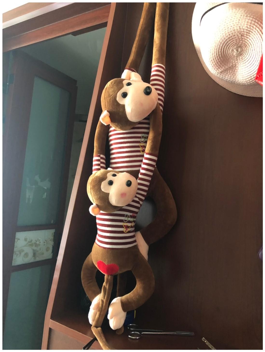 創意的なぬいぐるみの長い腕は伏せて猿のぬいぐるみの人形の小さい吊り子のかわいい子供は枕の女の子を抱きます。