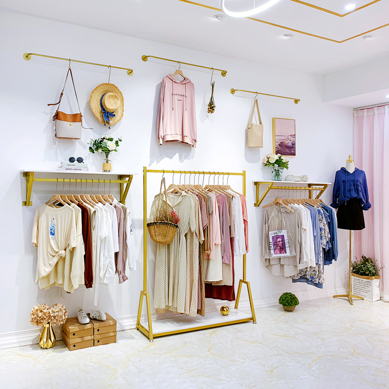 Hanging clothes and furniture display set of shelves store style clothing store womens clothing display simple gold wall hanging clothes rack