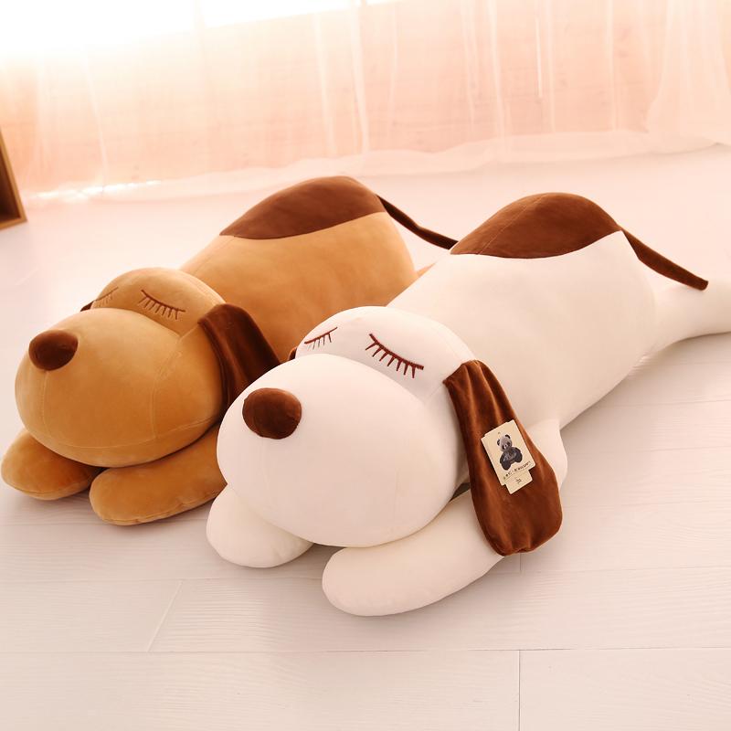 大きいサイズの犬のぬいぐるみを寝かせて子供のぬいぐるみを抱きます。可愛い女の子の日プレゼントです。