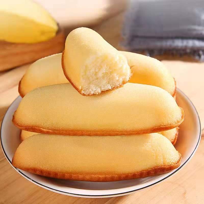 バナナのパンケーキ類のお菓子を一箱にまとめました。赤い午後、お茶の手でお菓子を引き裂いて手作りのお菓子を作ります。