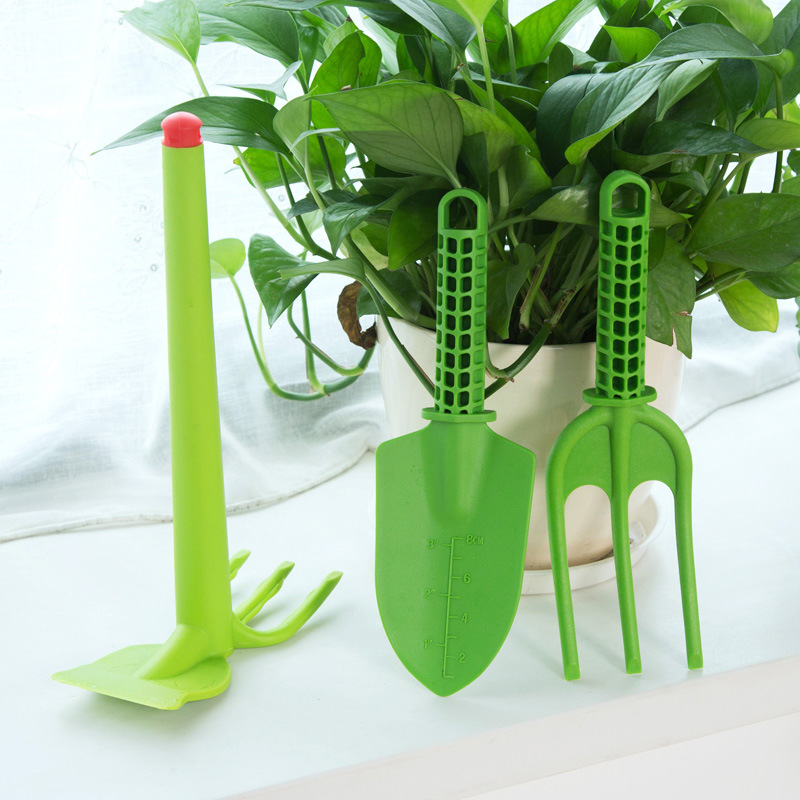 Childrens props, gardening tools, plastic hoes, flower supplies, and three sets of shovel hoes and flowers.