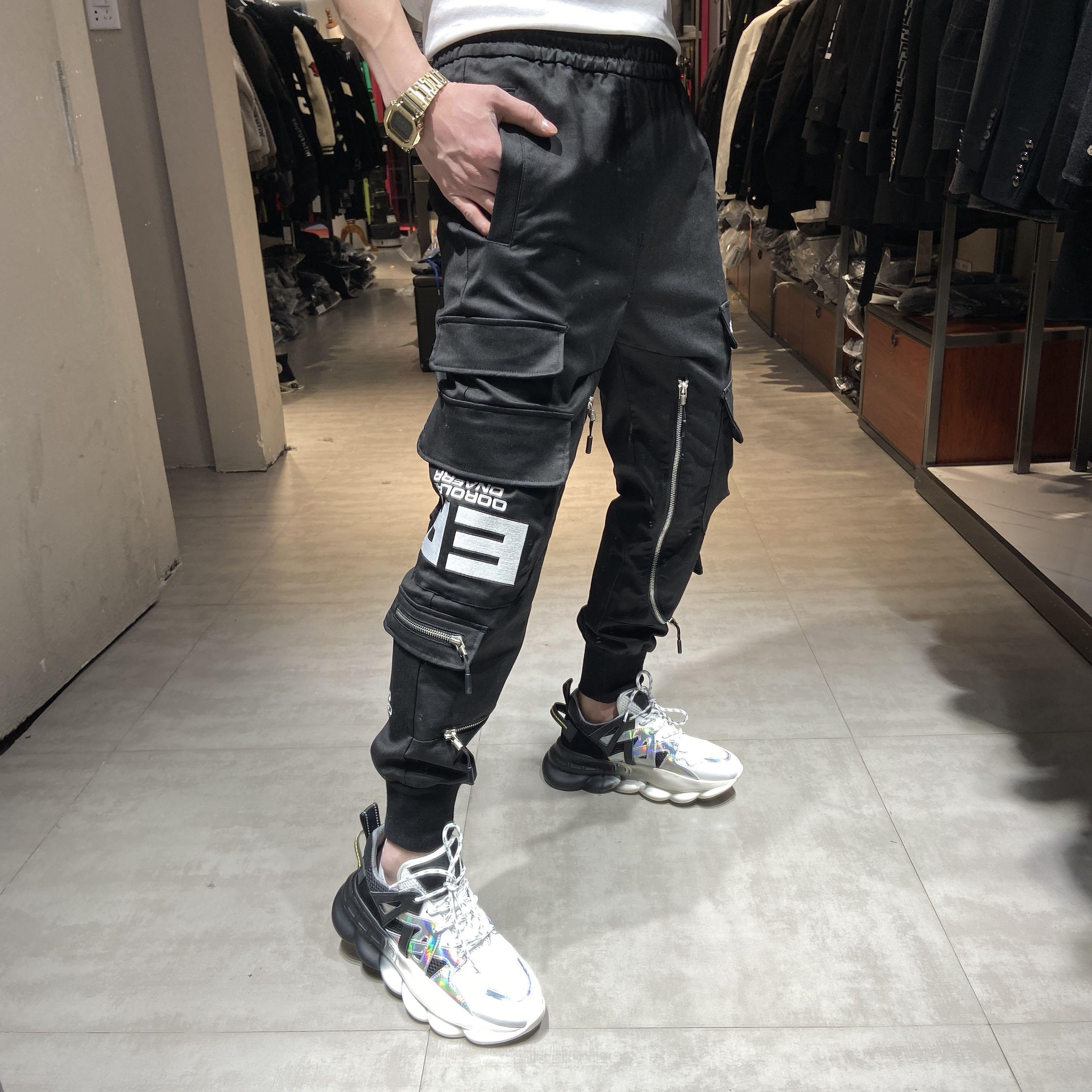 Quần yếm nam thương hiệu dầm chân mùa xuân Hàng châu Âu quần lỏng xu hướng Hàn Quốc cá tính dây kéo túi quần bình thường thủy triều - Quần mỏng