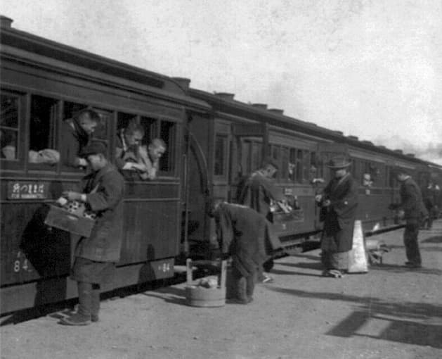 Passengers of train leaning out windows, being served refreshments by men on railroad platform.